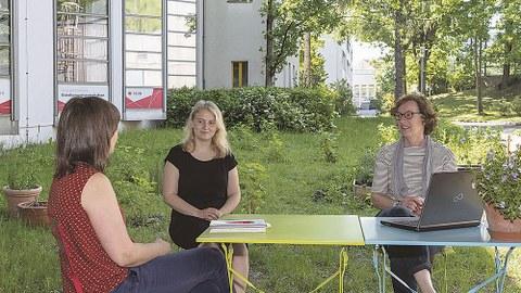 Die drei Frauen sitzen sich zugewandt an einem Gartentisch, auf dem ein Buch und ein Laptop stehen, im Gemeinschaftsgarten auf der Wiese.