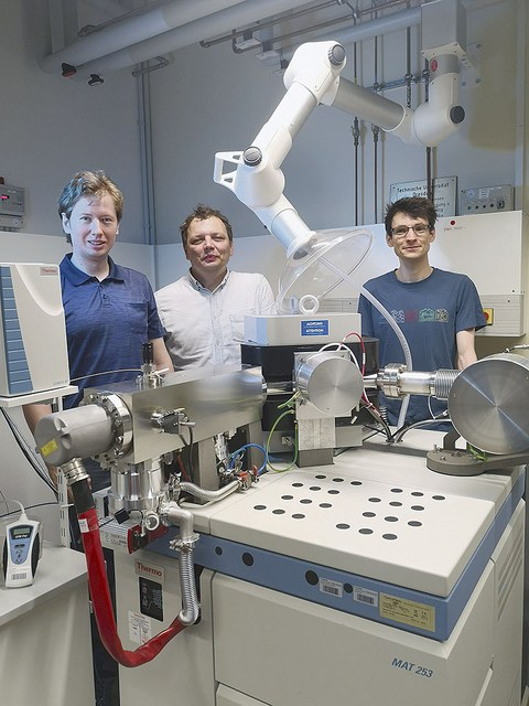 Stephan Beil, Björn Günther und Patrick Wordell-Dietrich stehen an einem Isotopen-Massenspektrometer mit Blick zum Betrachter.
