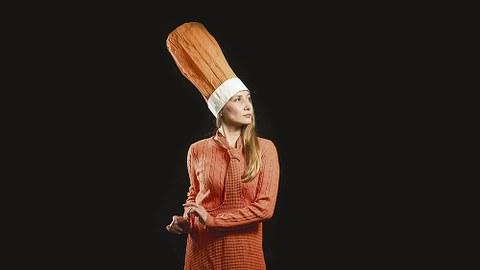 Anna Felsings Kopf und Oberkörper ist vor einem schwarzen Hintergrund fotografiert. Sie trägt einen orangefarbenen hohen Hut, einen gleichfarbigen Pullover sowie eine gleichfarbige Krawatte.