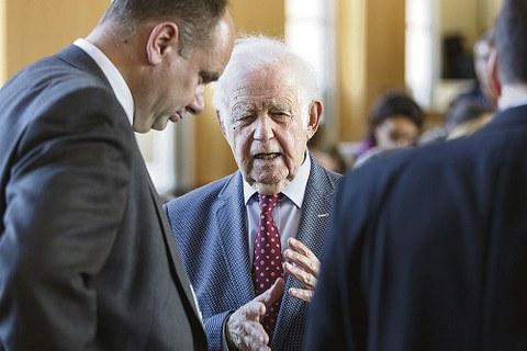 Prof. Kurt Biedenkopf spricht mit Dresdens Oberbürgermeister Dirk Hilbert. Prof. Biedenkopf ist von Vorne zu sehen, Dirk Hilbert steht vom Betrachter aus gesehen links neben ihm.