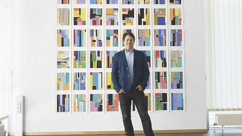 Anton Ginzburg steht vor seiner Serie. Diese besteht aus acht mal sechs kleinformatigen Bildern. Die Bilder sind geometrisch und bunt.