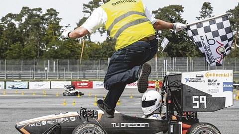 Ein Mann mit gelber Weste und schwarz-weiß-karierter Flagge in der Hand springt über einen Sportwagen. Darin sitzt ein Fahrer/eine Fahrerin.