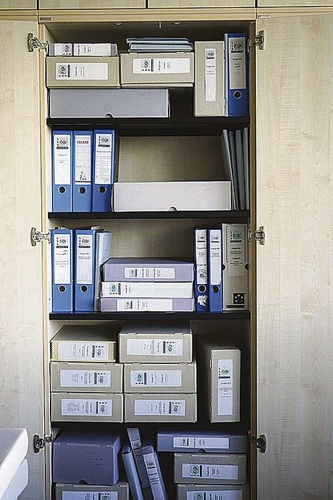 Zu sehen ist ein geöffneter Aktenschrank, in dem blaue Aktenordner und graufarbene Kisten stehen oder liegen.