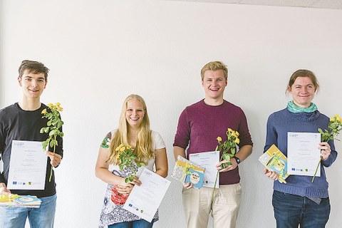 Die Gewinner stehen nebeneinander, halten ihre Urkunde und Blumen in der Hand.
