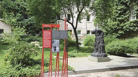 Links neben der Wieland-Förster-Plastik stehen auf roten Streben rote und graue Tafeln mit Texten.