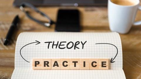 """Das Foto zeigt einen karierten Block mit dem geschriebenen Wort """"theroy"""". Mit aufgestellten Holzsteinen ist außerdem das Wort """"practice"""" dargestellt. Die beiden Worte sind durch Pfeile miteinander verbunden. Im Hintergrund ein Büroschreibtisch."""