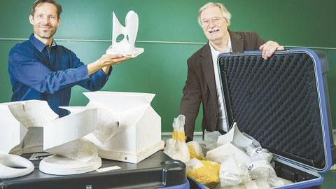 Daniel Lordick und Roland Seifert stehen hinter einem Tisch, auf dem die Modelle aufgebaut sind. Daniel Lordick hält eines in der Hand. Roland Seifert hält den Deckel des Transportkastens offen.