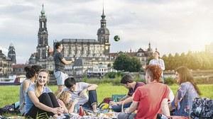 Eine Gruppe junger Menschen sitzt auf einer Wiese am Elbufer. Im Hintergrund spielen ein Mann und eine Frau Ball. Zu sehen ist die Silhouette Dresdens mit Hofkirche, Schloss und Italienischem Dörfchen.