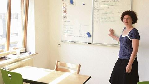 Die Förderschullehrerin Jeannine Ufer steht in einem Klassenraum vor einer weißen Wandtafel.