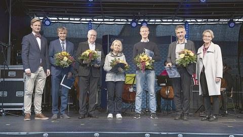 Die Ausgezeichneten stehen nebeneinander auf der Bühne und halten Blumen in der Hand.