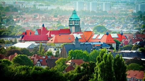 Luftaufnahme mit Bäumen vor dem Schumannbau und Wohnungen im Hintergrund