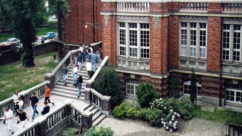 erhöhte Aufnahme von der Rückseite des Beyer-Baus mit kunstornamenten Ornamenten an der Backsteinwand und der Außentreppe, über die Studierende gehen.