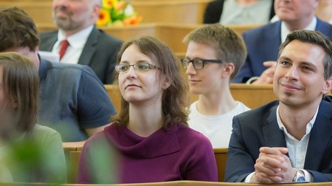 junge und ältere Menschen in guter Kleidung sitzen vergnügt in den Reihen eines Hörsaals.