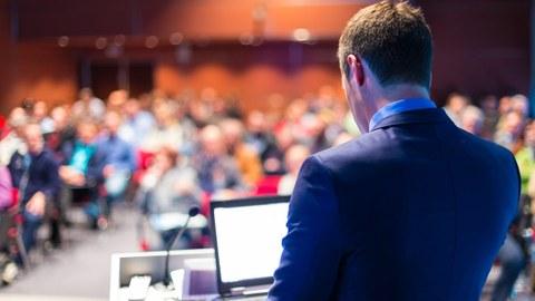 Vortragender mit laptop vor einem Publikum