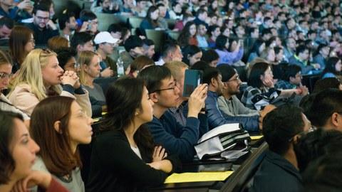 Internationale junge Leute sitzen in einem vollen Hörsaal