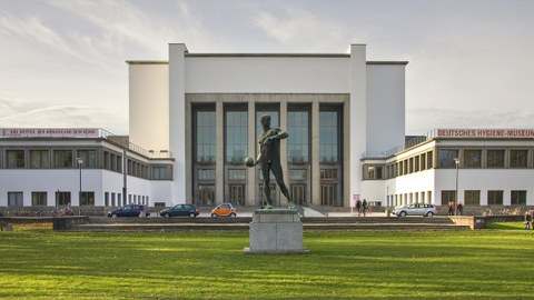 Quadratisches Gebäude mit Vorplatz und der Statue eines Sportlers