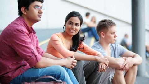 Drei Studierende auf den Treppen vor dem HSZ, ein Weißer