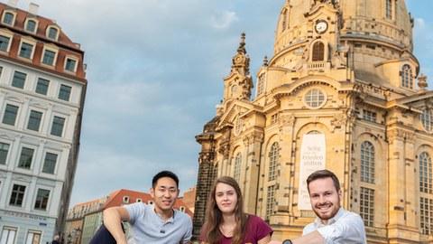drei junge Menschen sitzen auf dem Neumarkt vor der Frauenkirche