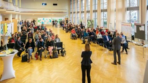 Dülfersaal am Tag von der Bühne aus aufgenommen, sitzendes Publikum vor einer Rednerin