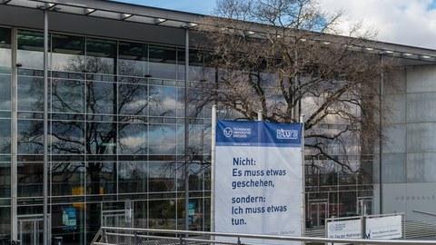 """Hörsaalzentrum im Herbst mit Banner im Vordergrund: """"Nicht 'estwas muss geschehen', sondern 'ich muss etwas tun'."""