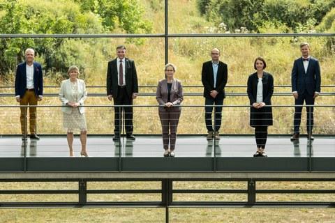 die sieben Mitglieder des erweiterten Rektorats stehen versetzt und mit Abstand in Anzügen und guter Kleidung auf einer Brücke vor einer grünen Wiese und Bäumen.