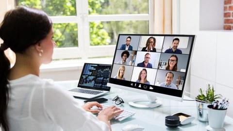 eine Frau schaut auf den Bildschirm in einer Videokonferenz