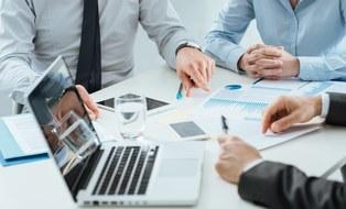 Foto eines Tisches mit Laptop und Händen von Meeting-Teilnehmenden