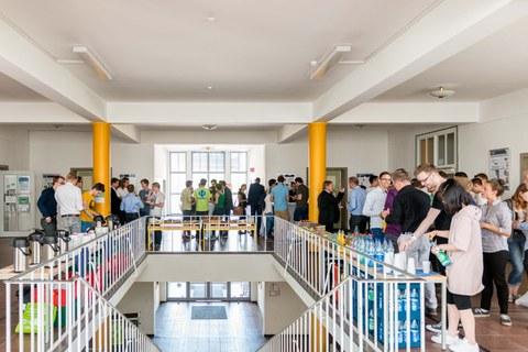 Foto einer Treppe, die in ein Foyer führt. Viele Studierende unterhalten sich dort und bedienen sich am Buffet.