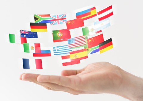 Hand hält internationale Flaggen