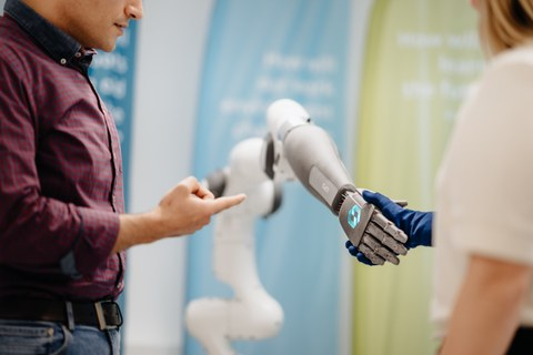 A man is cropped on the left, pointing with his index finger at a robot arm. At the right edge of the image, a woman can be seen cropped and out of focus. She is wearing a blue glove and shaking hands with the robot hand.