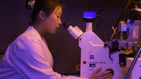 Studentin im Labor bei lila Beleuchtung