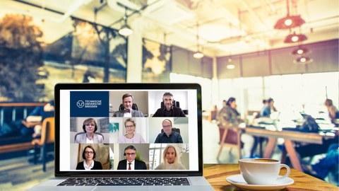 Computer auf einem Tisch in einem Cafe, auf dem die Mitglieder des Rektorats in einer Videokonferenz zu sehen sind