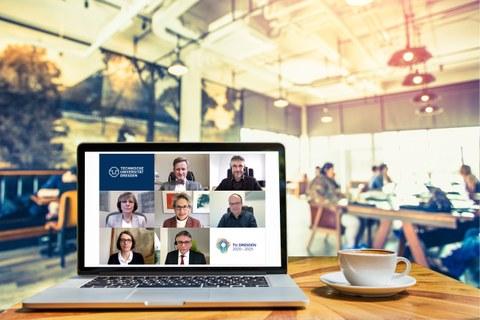 aufgeklappter Laptop auf Tisch in einem Cafe, auf dessen Bildschirm die Mitglieder des Erweiterten Rektorats in einer Videokonferenz zu sehen sind