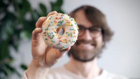 Mann im verschwommenen Hintergrund hält einen Donut in die Kamera