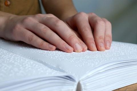 Foto eines Buches mit Brailleschrift, auf dem zwei Hände die Schriftzeichen berühren.