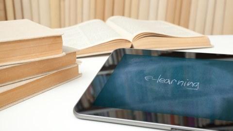 Foto eines Tisches, auf dem im Vordergrund ein Tablet liegt, im Hintergrund vier unerkennbare Bücher. Der Bildschirm des Tablet zeigt eine Tafeloberfläche sowie den Kreide-Schriftzug »e-learning«.
