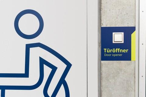 Foto eines Schalters beschriftet mit »Türöffner« neben einer geschlossenen Tür, auf der sich das Piktogramm eines Rollstuhlfahrers befindet.