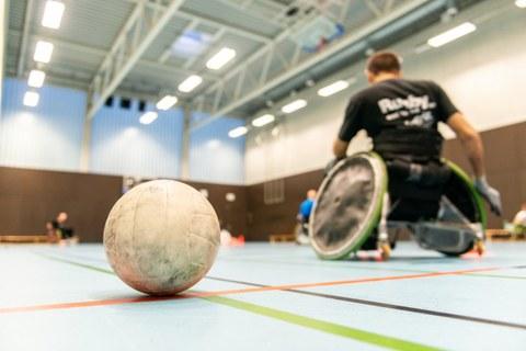 Foto einer Sporthalle. Im Vordergrund ein Handball, im Hintergrund unscharf mehrere Rollstuhlfahrer.