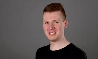 Zu sehen ist ein Porträtfoto des Mitarbeiters Eric Blumenthal.