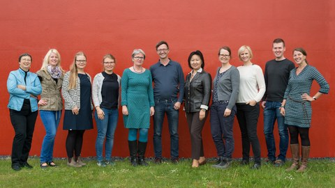 You can see a photo of a group of people. There are eleven people standing on a meadow in front of a red wall. Among them are two men and nine women. It is the team of the Central Student Information and Counselling Service.