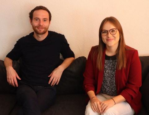 Das Foto zeigt zwei Personen, eine Frau und einen Mann, die zusammen auf einem Sofa sitzen.