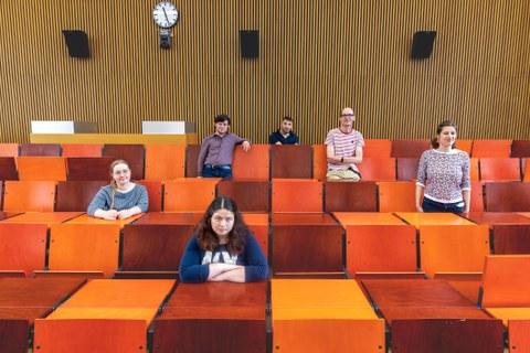 Das Foto zweigt eine Gruppe von 6 Personen, die in einem Vorlesungsaal mit orangenen Sitzgelegenheiten verteilt auf unterschiedliche Reihen sitzen oder stehen.