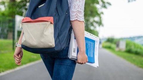 Ausschnitt einer Person von hinten mit Unterlagen im Arm