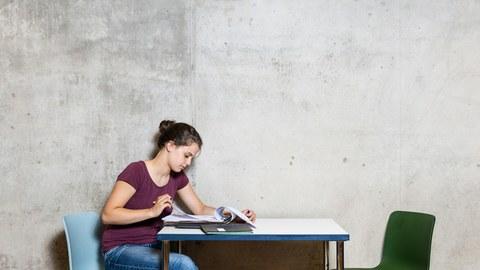 Seitenprofil einer Person an einem Tisch sitzend
