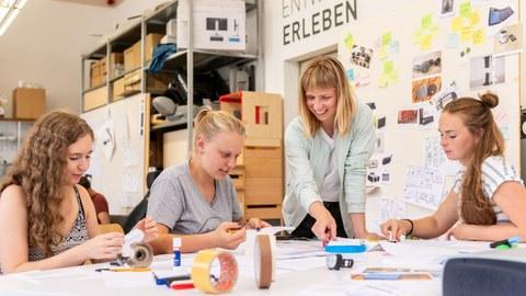 Vier Studentinnen arbeiten gemeinsam an einem Modell. Drei von ihnen sitzen, eine steht.