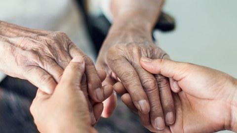 Das Foto zeigt die faltigen Hände einer älteren Person, welche in den Händen einer jüngeren Person leigen und von diesen umschlossen werden.