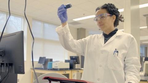 Das Bild zeigt die Wissenschaftlerin Raychelle Burks in ihrem Labor. Sie schaut auf eine Probe und trägt eine Schutzbrille und einen weißen Laborkittel.