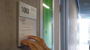 Ein Türschild, welches mit Braille-Aufdruck versehen ist und gelesen wird