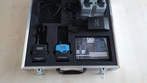 Photo of the suitcase, in which the Sennheiser technique is stored. The set consists of stereo transmitter, receiver and charging station.