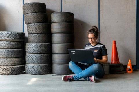 Frau sitz vor einem Reifenstapel mit einem Laptop in der Hand
